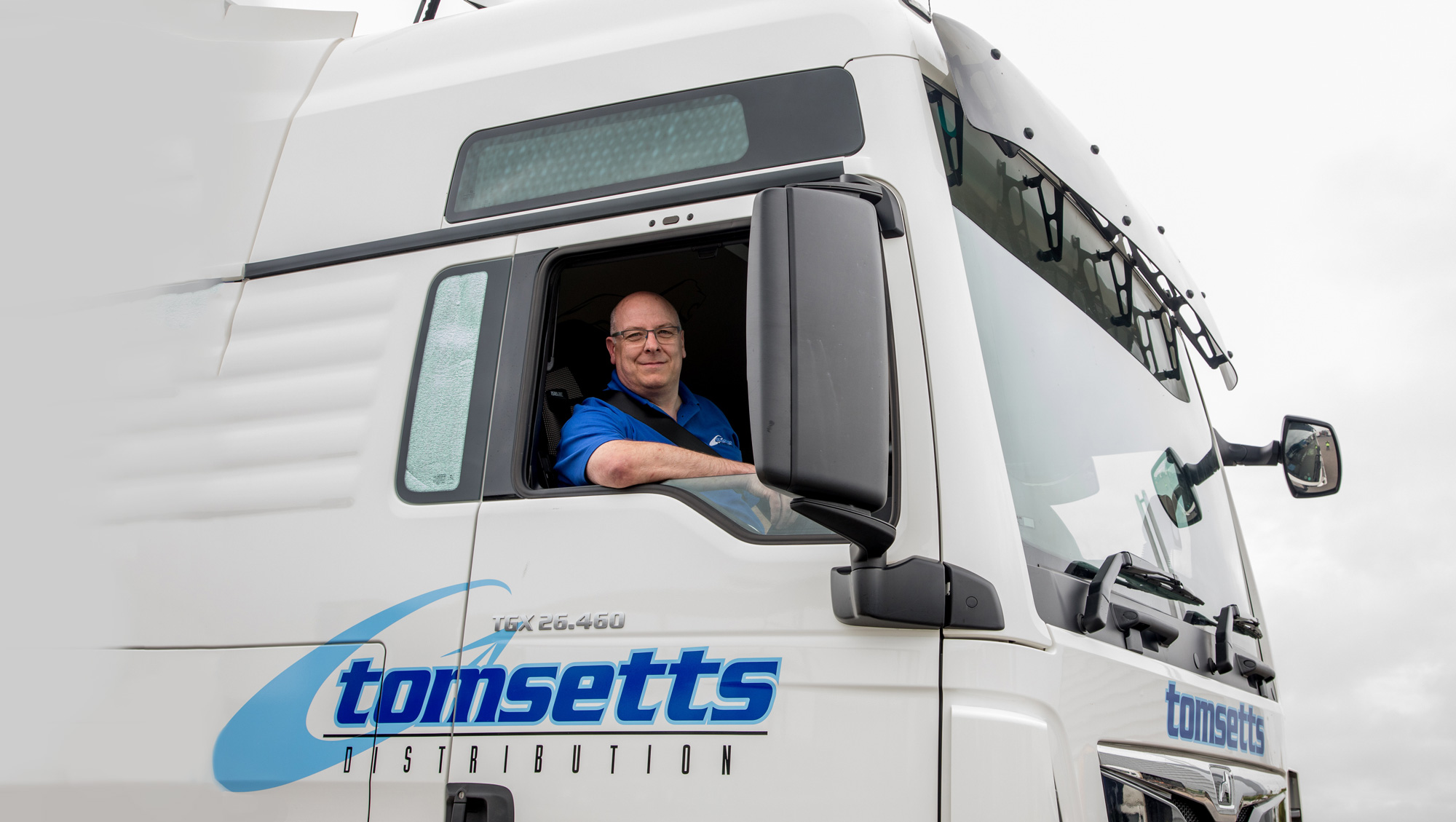 A lorry driver for Tomsetts pallet distribution poses for a picture within his new Tomsetts lorry