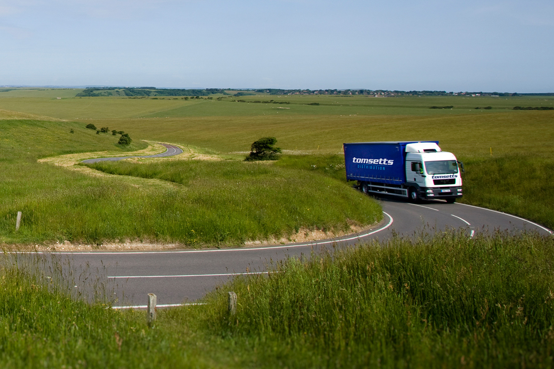 Environment friendly Tomsetts pallet distribution lorry drives through the countryside.